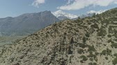 山頂 : Flight towards rocky bushy slope with old chorten, nearby Ngaval village, Nepal 動画素材