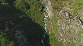 frightening : Overhead flight above green rocky river gorge, deep terrific precipice
