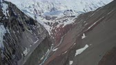 овраг : Atmospheric panoramic fly above river gorge near snowy mountain of Tilicho Peak