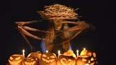 magik : Halloween costume woman, tree girl, female with hands branches with burning pumpkins in front of her over dark background Wideo