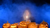 celebration : Girl in black coat and hood coming out from the blue smoke holding a candle to Halloween pumpkins