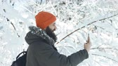 wintertime : Bearded hipster man outdoors in a winter snowy day texting in smartphone