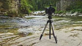 photography shot : Sliding video of professional photo camera mounted on tripod outdoors in moutain canyon in summer