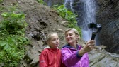 steadicam : Mouther and a child girl capturing themselves with small personal camera at mountain waterfall background