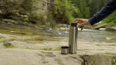 колба : Man hand pouring hot drink into a mug from the thermos, in the nature park, forest and mountain river at background Стоковые видеозаписи
