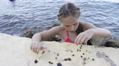 crustacea : Little girl playing with Paguroidea on a beach