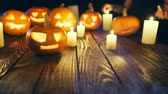 резной : Human hands firing candles Halloween pumpkins on weathered wooden planks, with smoke on foreground, blue back light, sliding video