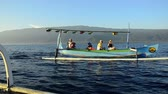 colina : Tejakula Bali - Indonesia: March 2013: Tourists in a indonesian fisher-catamaran called Jukung. They will drive to a watching area of  wild dolphins. In the background the vulcano hills of Bali in sunrise.