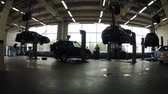 carcare : MOSCOW - AUG 27: (Timelapse View) Four cars are fixed on lifting-jack hoist in garage of Dealership Automir, on Aug 27, 2012 in Moscow, Russia. Automir represents 21 leading automobile brands