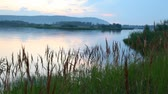 ling : evening landscape of lake with thickets both green woods and mountains in distance Stock Footage