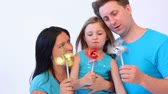 shoulder blades : Mother, father and daughter playing with toy windmills Stock Footage