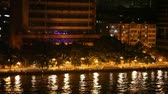 Pearl River embankment with a passing car, lights reflected in the water