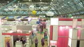 посылка : In exhibition centre people approach to stands to receive the information, the top view