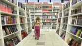 regał : little cute girl with shopping trolley walking in bookshop