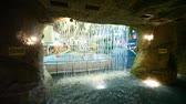 waterworks : Through a waterfall of dark stone cave seen people bathing in pool in indoor waterpark