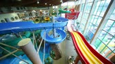 waterworks : People rapidly slide down a wet red and blue plastic hills in large indoor water park