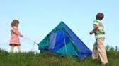 kids tent : boy and his kid sister tenting against blue sky outdoors