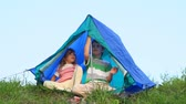 kids tent : boy and his kid sister sits under tent out of town Stock Footage