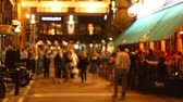 Out of focus view on many people walking on a street with many bars of Dublin in evening time  Vídeos