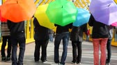 onda : young men spin colorful umbrellas back to camera then jump up Stock Footage