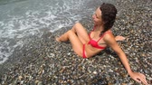 pretty : happy woman dressed in bikini sitting on pebble beach with sea surf
