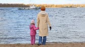 parent : woman with little girl on sandy bank waving one hand to boat moving in river