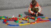 miniatura : little boy collects structure of plastic toy railway in street on asphalt Stock Footage