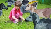 irreal : girl on lawn feeds with grass drawn silhouette of nanny-goat Stock Footage