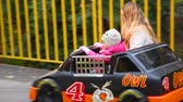 parent : young mother and her little daughter sits in moving car in amusement park