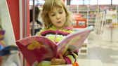regał : surprised little cute girl looking at childs book in bookshop Wideo