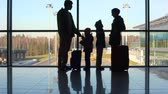 family of four stands against window at airport, then comes out Stok Video