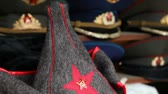 disposição : Many souvenir military caps with Soviet and Russian symbols and budenovka are on counter in a shop Vídeos