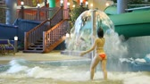 waterworks : Charming woman in orange swimsuit runs under fountain in a pool in indoor water park