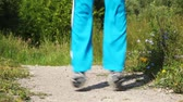 carry out : Close up of feet of girl who are carrying out exercises on road in park