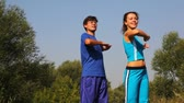 carry out : man and woman carries out exercises in park together