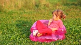 kitapçık : girl sit in childrens inflatable armchair in park and gnaws pen Stok Video
