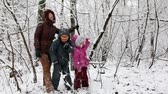 sister : Mother with two children in snow forest shakes snow from branches