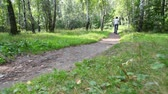parent : boy and man rides bicycles on pathway in summer forest from camera