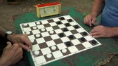 frayed : People play checkers with time limit on table with worn surface, and then girl cames