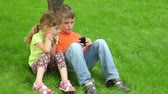 sister : Two kids boy and girl sit together at grass near tree, sister watches how her brother plays with digital game on cell phone Stock Footage
