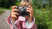 снимок : portrait of little girl with photo camera in park