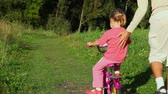 parent : father helps a little daughter riding bicycle in summer park