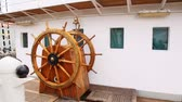 against window : Old steering wheel from wood stands on sailing vessel deck Krusenstern against captain cabin