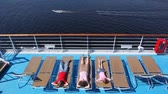 couch : Mother, son with daughter lie in chaise lounge on liner deck
