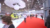 nagylátószögű : MOSCOW - MAY 21: Visitors go along helicopters exposed on International exhibition of helicopter industry of Helirussia in Exhibition center Expo Crocus, on May 21, 2012 in Moscow, Russia Stock mozgókép