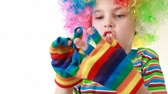 berrante : Boy in a ridiculous multicolor wig wears gaudy striped gloves