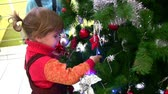 campanário : Little girl watching christmas tree in shop Stock Footage