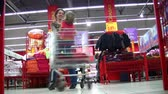 parent : Mother rotates child in shopping cart in shop Stock Footage