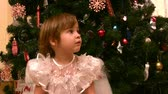 campanário : Little girl sits on chair near christmas tree Stock Footage