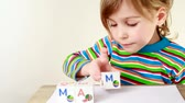 мама : Girl in multicolor striped T-shirt puts together cubes with letters for obtaining word Mama Стоковые видеозаписи